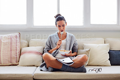 Buy stock photo Shot of a beautiful young woman going over some work while having breakfast in the morning at home