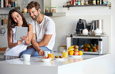 Buy stock photo Shot of a young couple using a digital tablet together during their morning routine at home