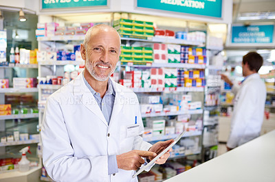 Buy stock photo Portrait of a mature pharmacist using a digital tablet while in a chemist
