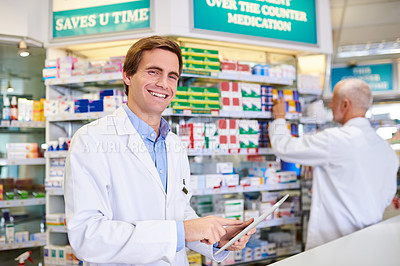 Buy stock photo Portrait of a young pharmacist using a digital tablet while in a chemist