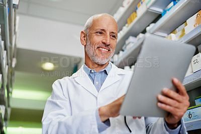 Buy stock photo Shot of a mature pharmacist using a digital tablet in a pharmacy