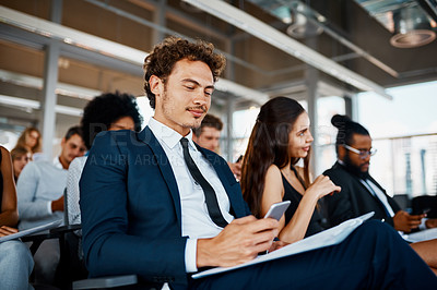 Buy stock photo Cropped shot of a handsome young businessman using his cellphone during a seminar in the conference room