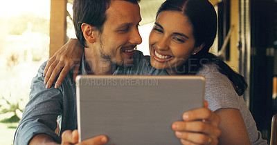 Buy stock photo Cropped shot of a young attractive couple using a tablet at home