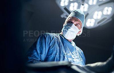 Buy stock photo Shot of a surgeon performing a surgery in an operating theatre