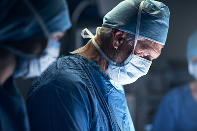 Buy stock photo Shot of surgeons performing surgery in an operating theatre
