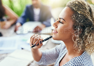 Buy stock photo Shot of a young businesswoman looking thoughtful while having a meeting with her colleagues outdoors