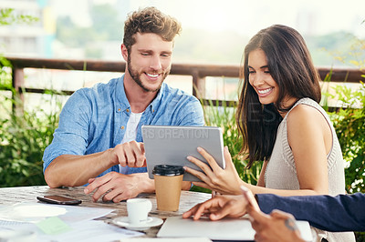 Buy stock photo Shot of businesspeople using a digital tablet during a meeting outdoors