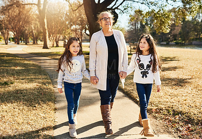 Buy stock photo Shot of a grandmother walking with her adorable granddaughters outdoors