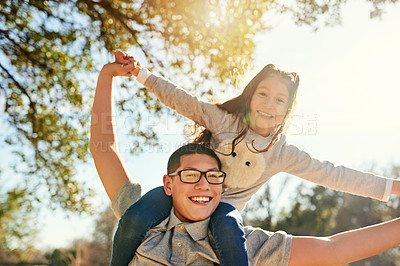 Buy stock photo Low angle shot of a teenage boy carrying his adorable little sister on his shoulders outdoors