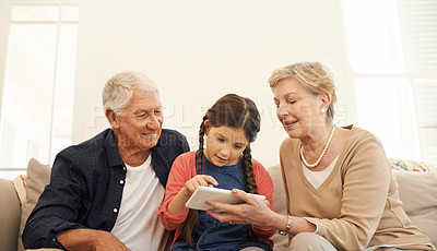 Buy stock photo Shot of a little girl using a digital tablet with her grandparents on the sofa at home