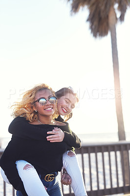 Buy stock photo Cropped shot of two female best friends having fun together at the beach