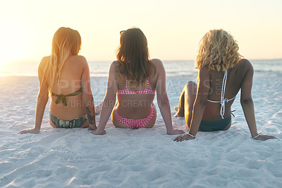 Buy stock photo Rearview shot of unrecognizable female best friends spending the day at the beach