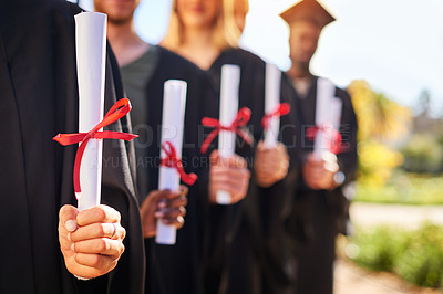 Buy stock photo Closeup shot of a group of unrecognizable students holding their diplomas on graduation day