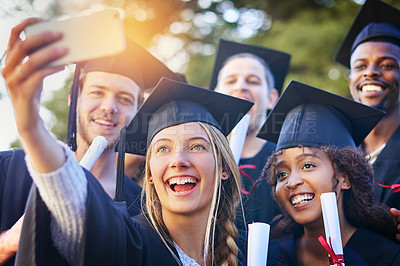 Buy stock photo Cropped shot of a group of university students taking a selfie on graduation day