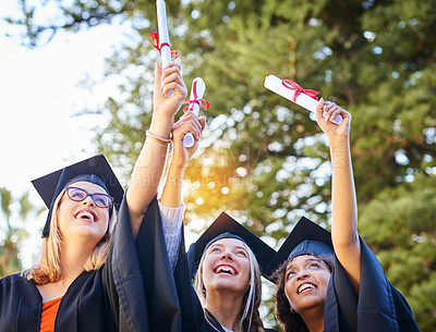 Buy stock photo Shot of a group of graduates holding their diplomas up in the air