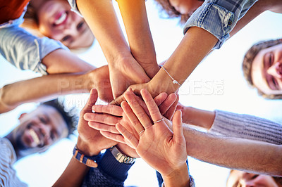Buy stock photo Low angle shot of university students standing outside with their hands together