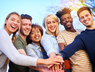 Buy stock photo Cropped shot of a group of diverse students huddled together with their hands piled on top of each other