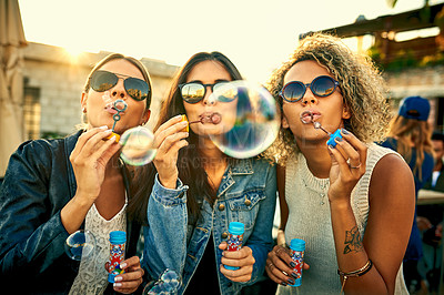 Buy stock photo Shot of a group of young women blowing bubbles together outdoors