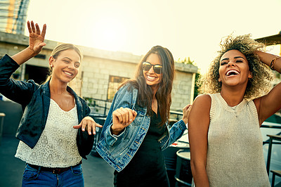 Buy stock photo Shot of a group of young women dancing and having fun together outdoors