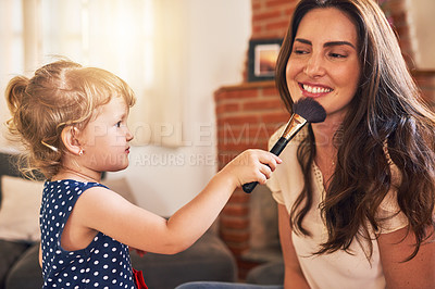 Buy stock photo Shot of an adorable little girl applying makeup to her mother's face at home