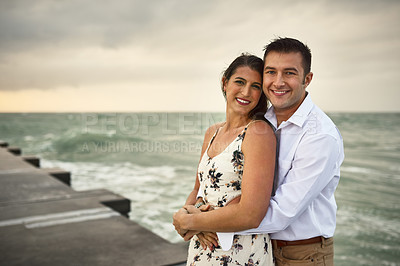 Buy stock photo Cropped portrait of an affectionate young couple standing on the jetty at the beach