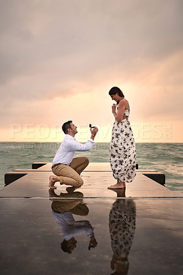 Buy stock photo Full length shot of a handsome young man proposing to his girlfriend on the jetty at the beach