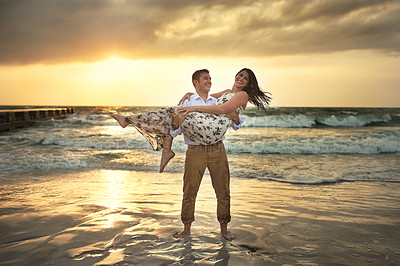 Buy stock photo Full length shot of a handsome young man carrying his girlfriend on the beach
