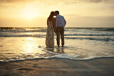 Buy stock photo Rearview shot of an affectionate young couple holding hands while kissing on the beach