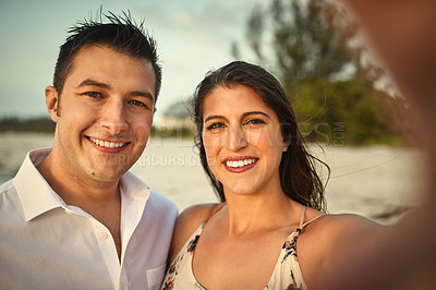 Buy stock photo Cropped portrait of an affectionate young couple taking selfies while standing on the beach