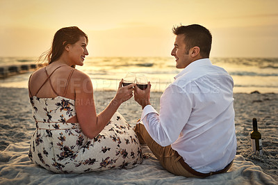 Buy stock photo Rearview shot of an affectionate young couple enjoying some wine while sitting on the beach