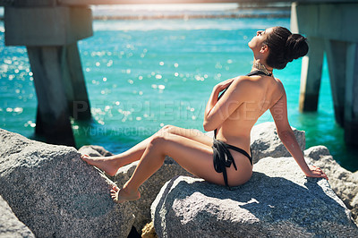 Buy stock photo Shot of a beautiful young woman in her bathing suit at the beach