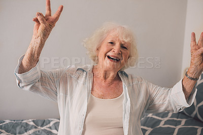 Buy stock photo Shot of a happy senior woman making a peace gesture in an old age home