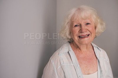 Buy stock photo Shot of a happy senior woman leaning against a gray wall