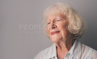 Buy stock photo Shot of a senior woman looking content against a gray background