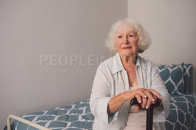 Buy stock photo Shot of a senior woman with a cane looking thoughtful in her bedroom at a retirement home