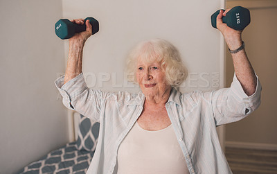 Buy stock photo Shot of a senior woman exercising with weights in a retirement home