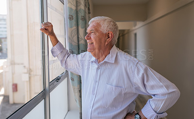 Buy stock photo Shot of a senior man looking out of a window in a retirement home