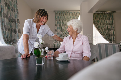 Buy stock photo Shot of a senior woman talking to a nurse while having coffee at a retirement home