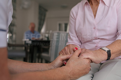 Buy stock photo Copped shot of a senior woman and a nurse holding hands in a retirement home