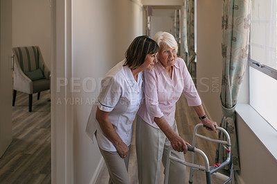Buy stock photo Shot of a nurse taking a senior woman for a walk with her walker in a retirement home