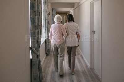 Buy stock photo Rearview shot of a senior woman and a nurse going for a walk in a retirement home