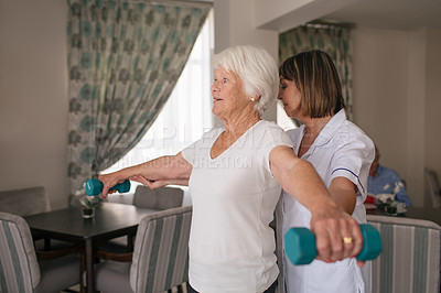 Buy stock photo Shot of a nurse helping a senior woman workout with weights in a retirement home