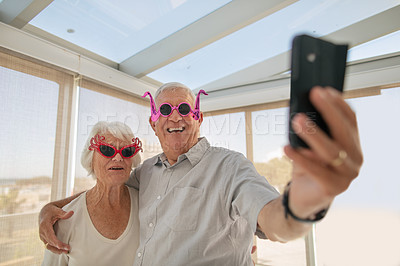 Buy stock photo Shot of a senior couple taking a selfie while wearing funky sunglasses in a retirement home