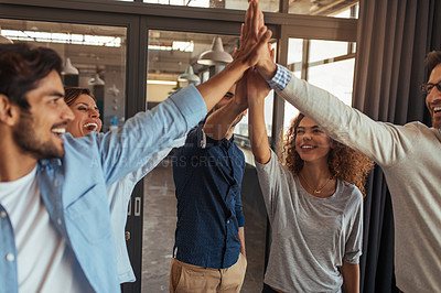 Buy stock photo Shot of a group of businesspeople high fiving each other in an office