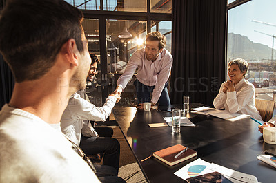 Buy stock photo Shot of businesspeople shaking hands during a boardroom meeting in an office