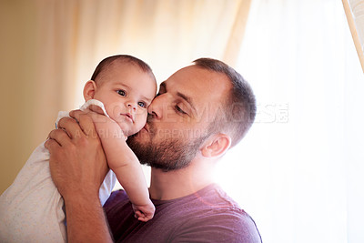 Buy stock photo Shot of a young man bonding with his adorable baby girl at home