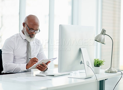 Buy stock photo Cropped shot of a handsome mature businessman writing in his notebook while working in the office