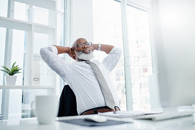 Buy stock photo Cropped shot of a handsome mature businessman looking relaxed while working on his computer in the office