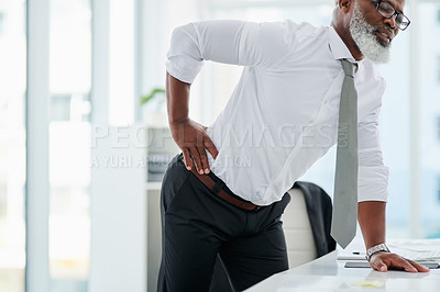 Buy stock photo Cropped shot of a mature businessman suffering with backache while working at his desk in the office