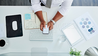 Buy stock photo High angle shot of an unrecognizable businessman sending a text while working at his desk in the office